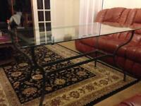 Glass table with dark grey metal frame.