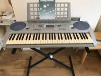 Yamaha keyboard with stand and music book