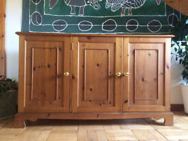 Dining/living room sideboard, antiqued pine. Three doors with brass handles, shelves inside.