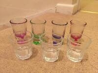 Seven shot glasses - three clear, four colours: red, green, pink, purple