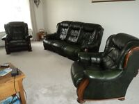 Green leather 3 piece suite with solid frame and wood trim. 3 seater sofa. Padded back and seats.
