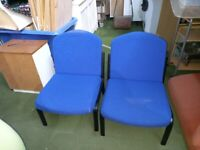 2 metal framed chairs with blue padded seats and backs