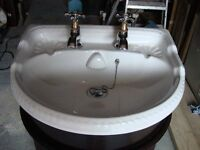 ceramic sink with chrome and gold taps in a dark mahogany unit