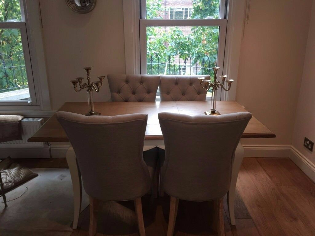 an extendable wooden dining table with 4 modern light grey dining chairs