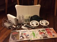 Wii console, 2 controllers, balance board, 2 steering wheels & 5 games. Used, good working order