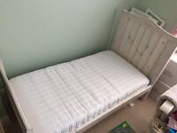 White cotbed with mattress and storage drawer