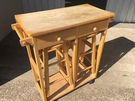 Compact dining table and two stools.