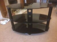 "Black glass television stand with three shelves 31"" wide x 18"" deep x 21"" high."