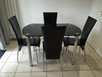 Black glass extendable dining table and 4 chairs, extends to round table.