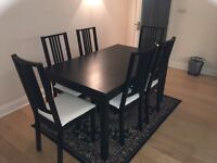 Black dining room table and 6 black and white cushioned chairs Excellent condition