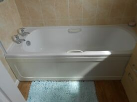 White bath with handles, side panel and taps