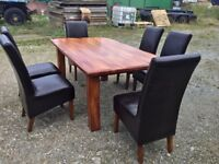 Solid hardwood dining table and 6 leather bound chairs.