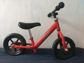 Red child's Trax balance bike.
