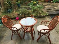 Round glass table and 2 wicker chairs ideal for a conservatory or patio