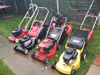 Job lot of petrol lawn mowers with grass boxes,+ some spare engines and a crate of spare parts