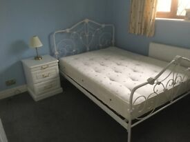 White double bed and bedside table.