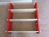 3 shelf wall display unit with red metal side frame and light veneer shelves.