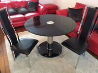 Four seater black glass dinning table and chairs
