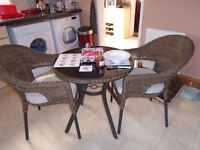 Lovely wicker, glass top table and 2 wicker chairs with cushions