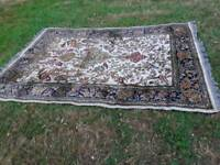Large rug in a colourway of beige background and greens and cream pattern