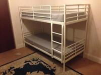 Ikea white metal bunk beds with mattresses.