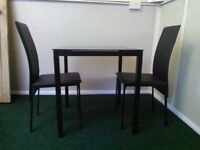 black glass table and 2 chairs