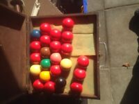 Full sized snooker balls including a spare cue ball in a wooden case