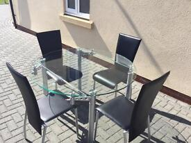 Glass dining table with four faux leather chairs