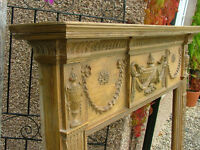 A large ornate carved pine fire surround