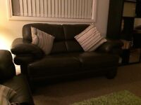 Two seater leather sofa and footstool for sale.