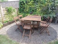 Wooden patio set with six folding chairs which store under the table for space-saving