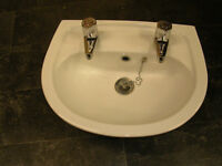 small white wall hung wash basin with chrome taps