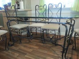 Immaculate glass dining table and 6 cream upholstered chairs
