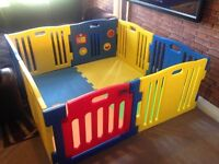 8 panel playpen with rubber floor mat, toys on one panel, opening gate