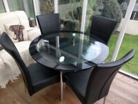 Round glass dining table with 4 leather chairs