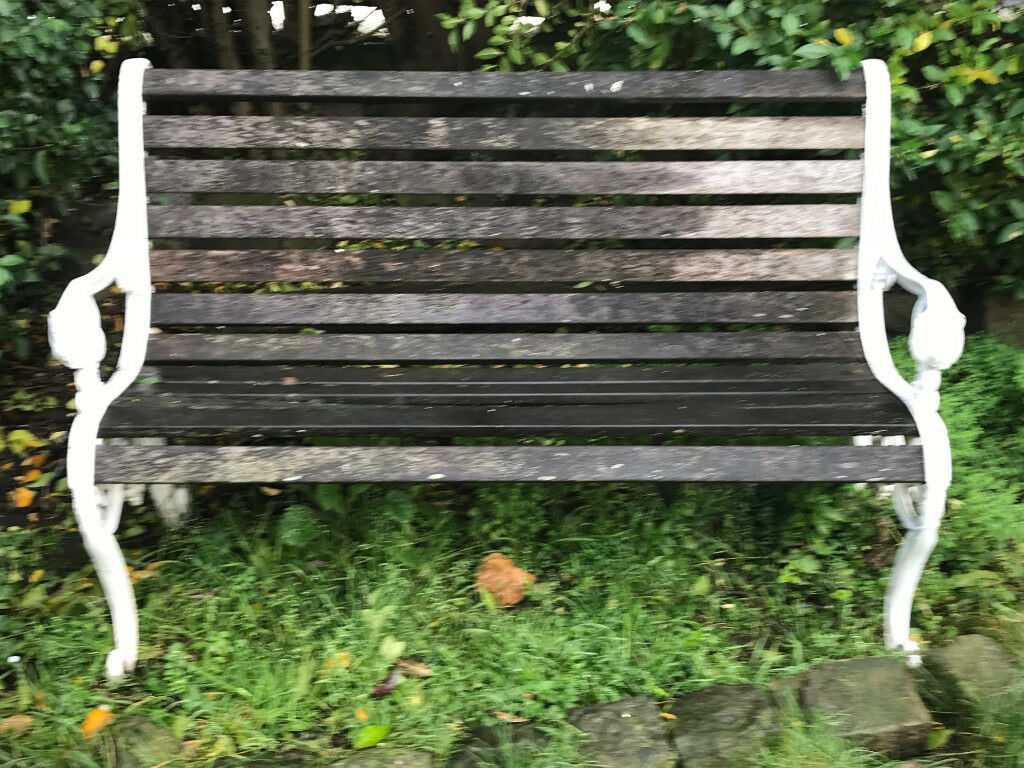 Garden Bench With White Ornate Wrought Iron Armrests In