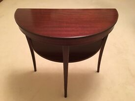 A 'Legate' mahogany demi lune table with undertier, on tapering sabre supports,