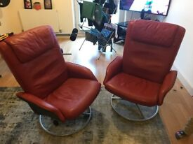 Two red leather swivel & reclining chairs