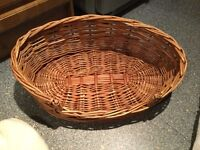 """Strong wicker dog/cat basket with cushion and throw over. 22.5"""" wide by 15"""" approx front to back."""