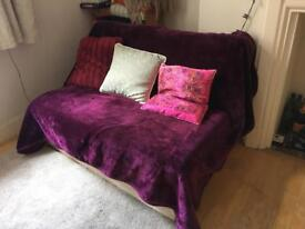 Two seater sofa bed with throw-over and cushions