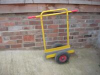 Board trolley with pneumatic wheels and support bar