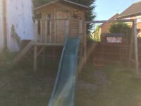 Wooden playhouse with slide