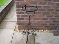 A black metal planter holder