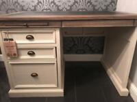 Reclaimed cream and brown wooden desk with black surfacing on top.