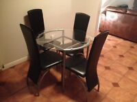 Round glass dining table with four black leather chairs for sale