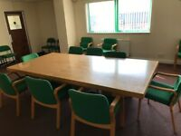 large wooden conference table with 12 chairs