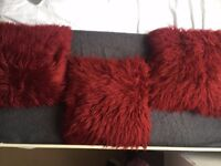 Three wine red fluffy pillows