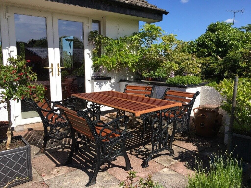 Black wrought iron and wood patio set table and four chairs good condition penrith