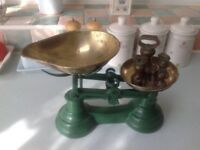 Dark green old fashion type kitchen scales complete with all its weights makes a great ornament .