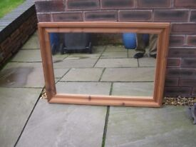 A large rectangular pine framed mirror.